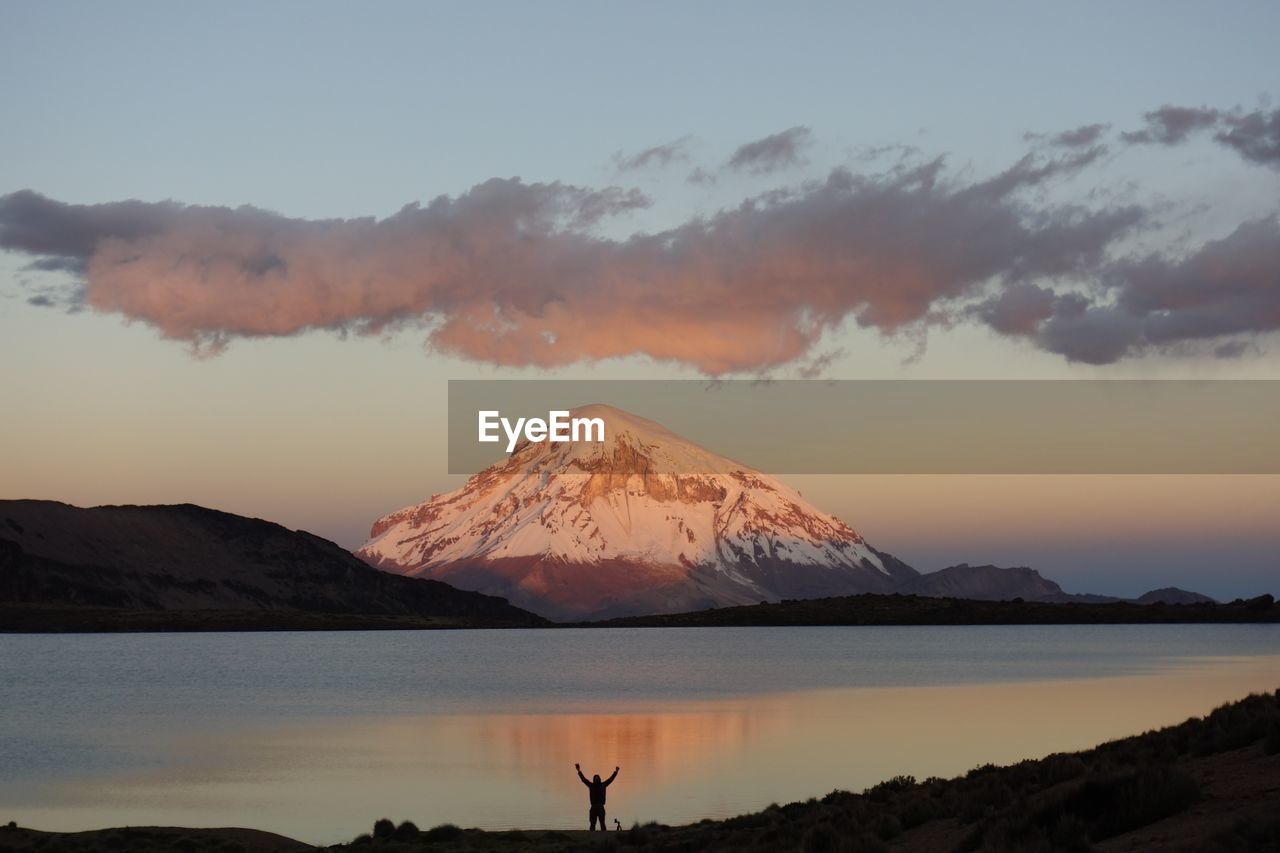 Scenic View Of Snowcapped Mountain By Lake During Sunset