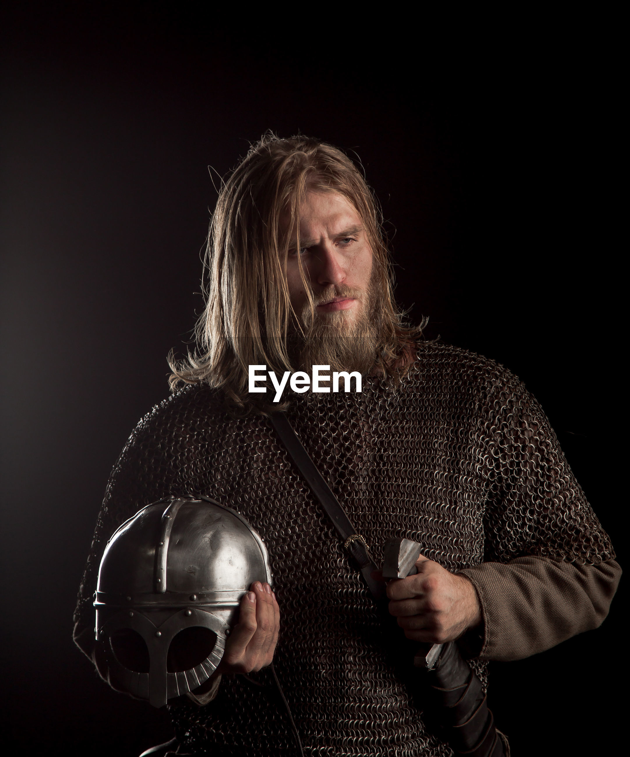 Viking with helmet and sword against black background