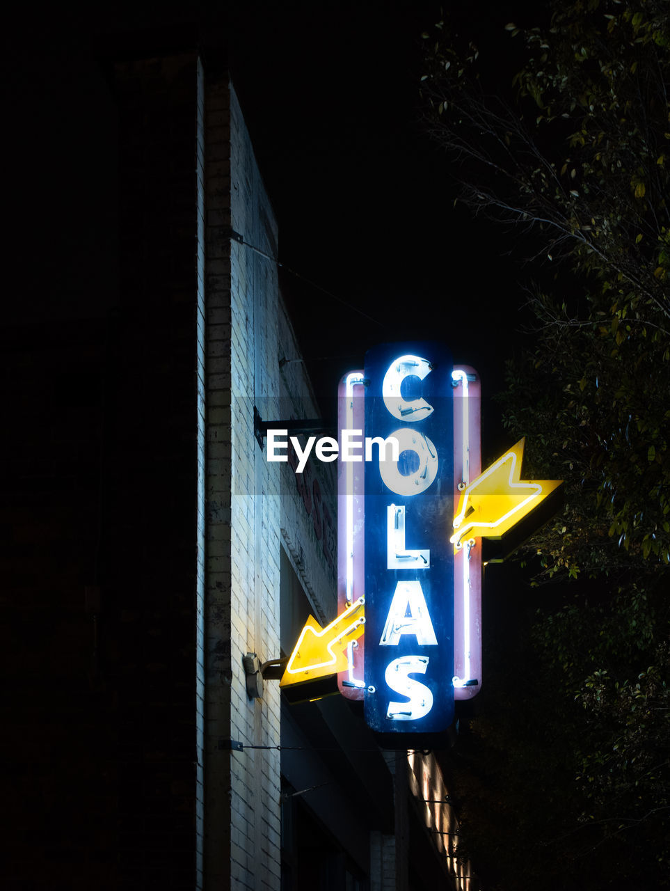 LOW ANGLE VIEW OF ILLUMINATED SIGN AGAINST WALL AT NIGHT