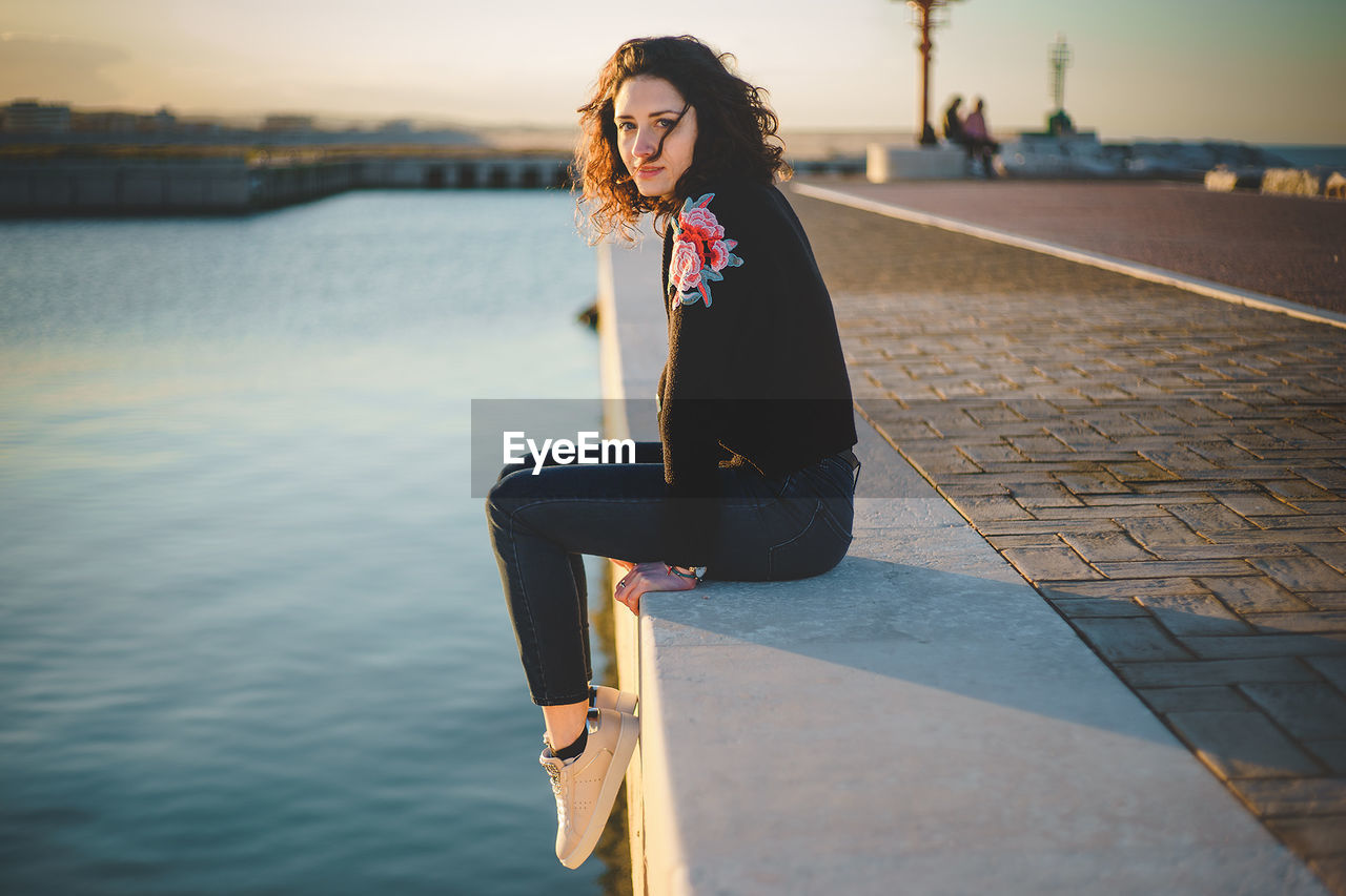 Portrait Of Woman Sitting On Retaining Wall Over Sea During Sunset