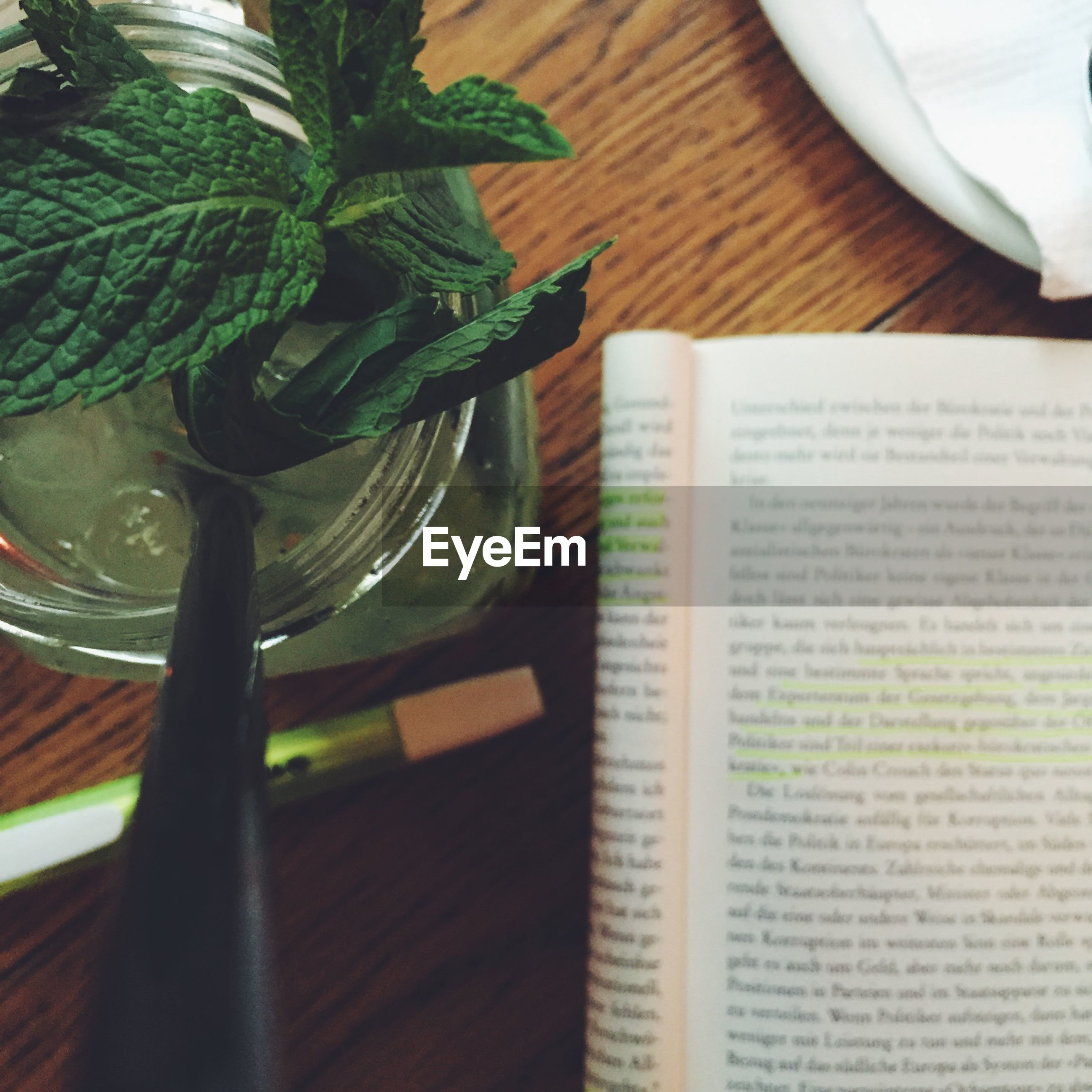 High angle view of iced tea by book on table