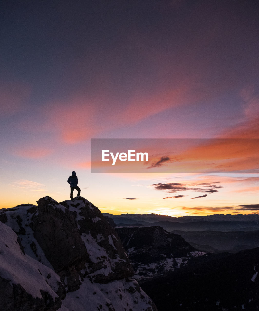 Silhouette Of Man On Mountain Peak Against Sky At Sunset