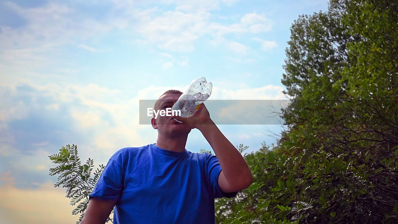 Man Looking Away While Drinking Water From Bottle Against Sky