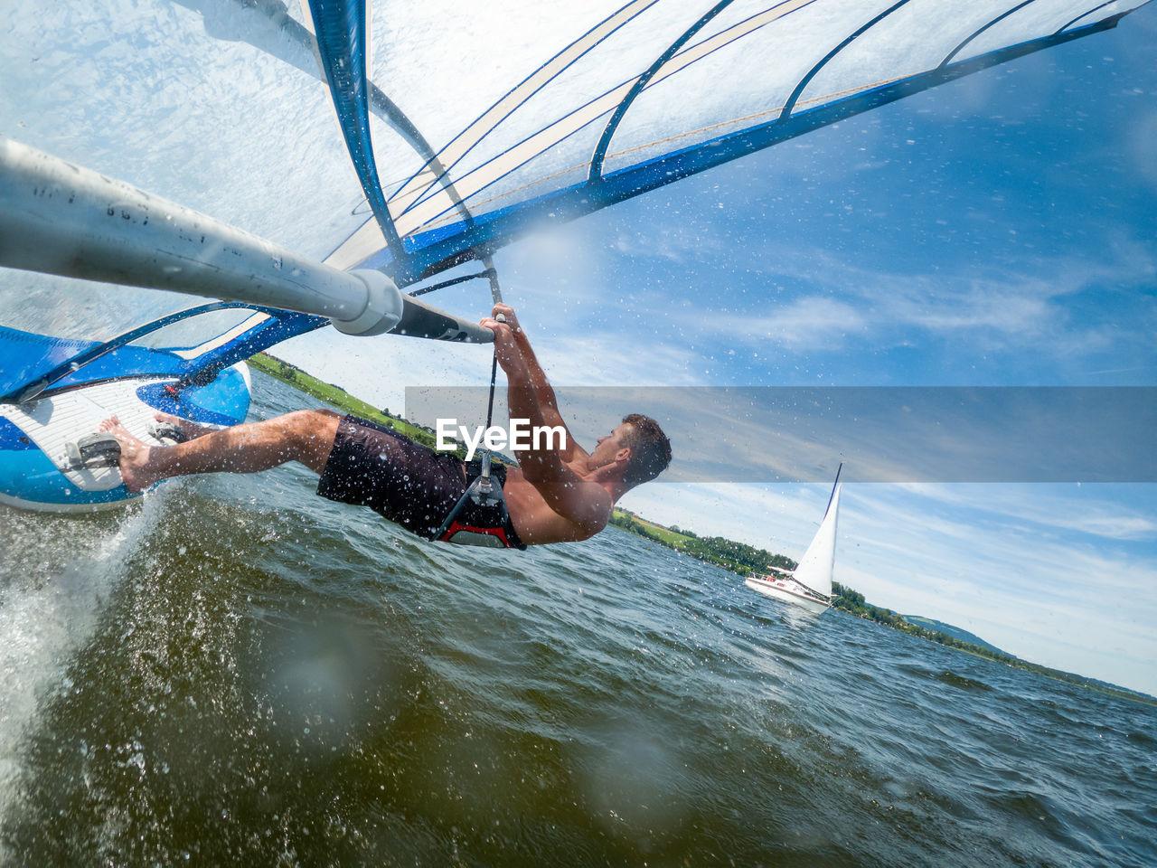 MAN SPLASHING WATER IN SEA
