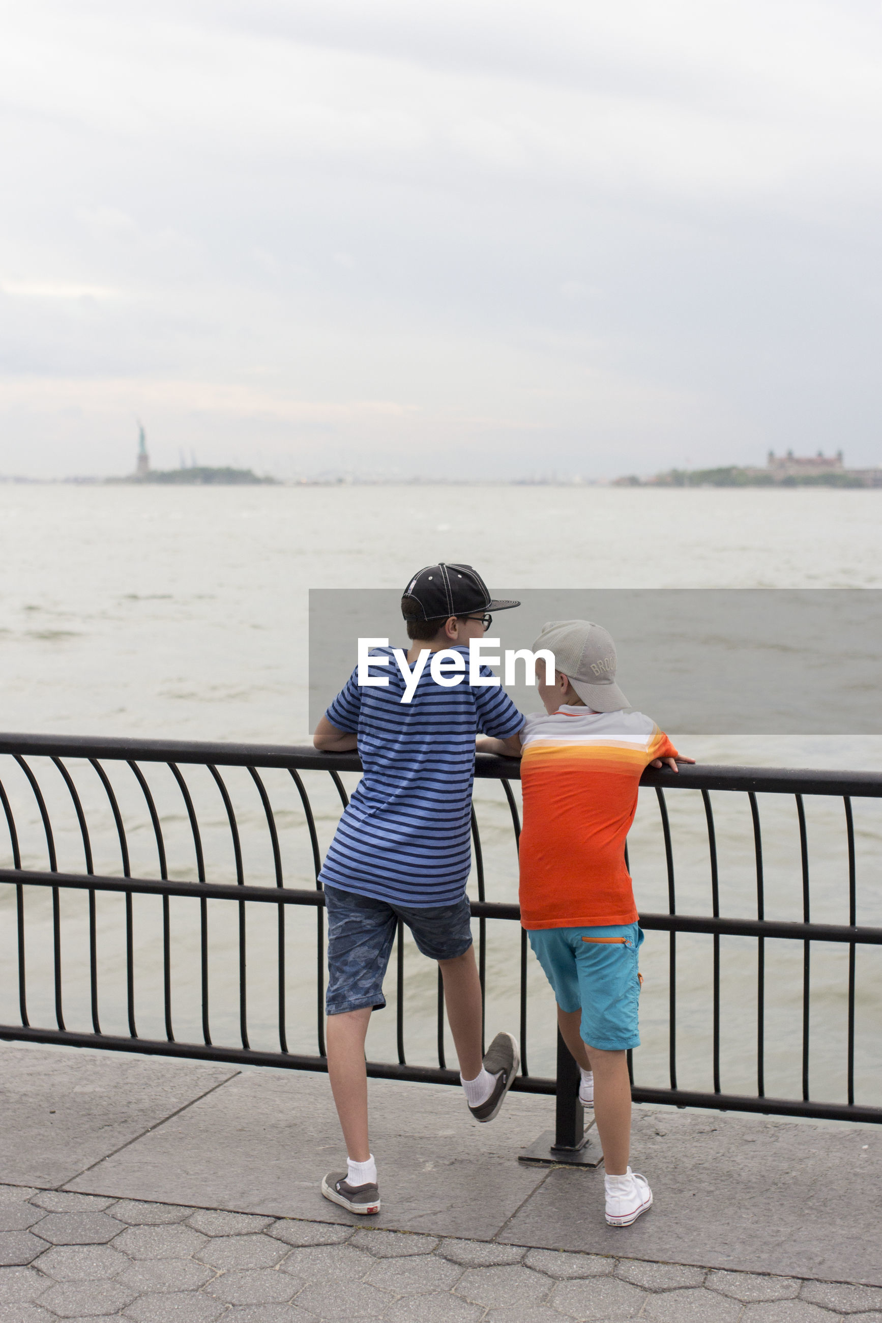 FULL LENGTH OF BOYS LOOKING AT SEA AGAINST SKY