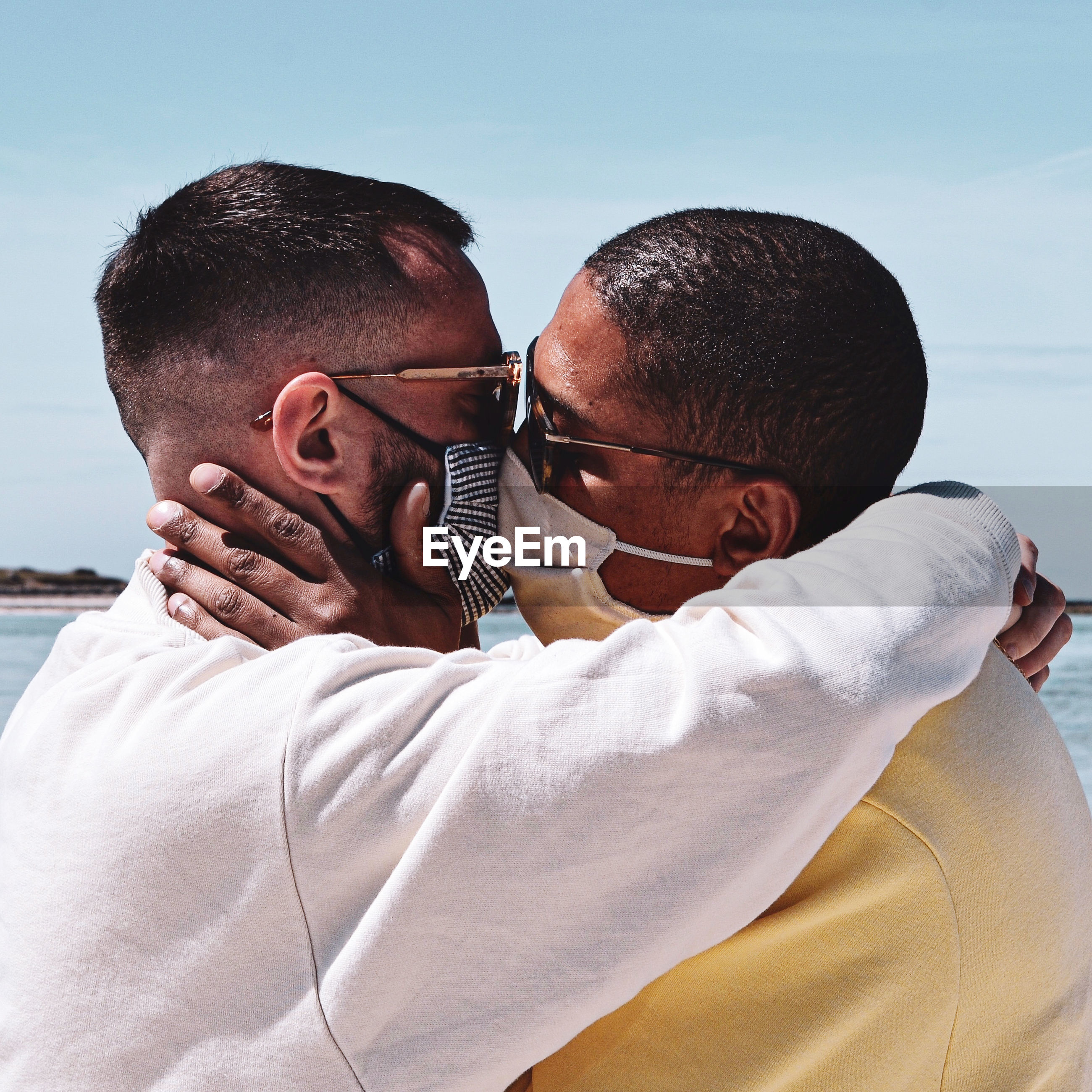 Gay couple wearing masks kissing against sky