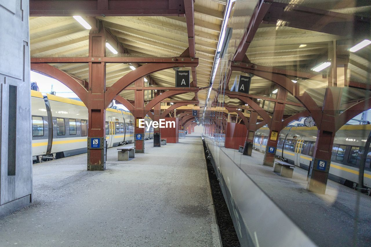 architecture, built structure, transportation, rail transportation, public transportation, illuminated, direction, railroad station, architectural column, indoors, empty, the way forward, ceiling, railroad station platform, no people, mode of transportation, track, lighting equipment, diminishing perspective, railroad track, light, station
