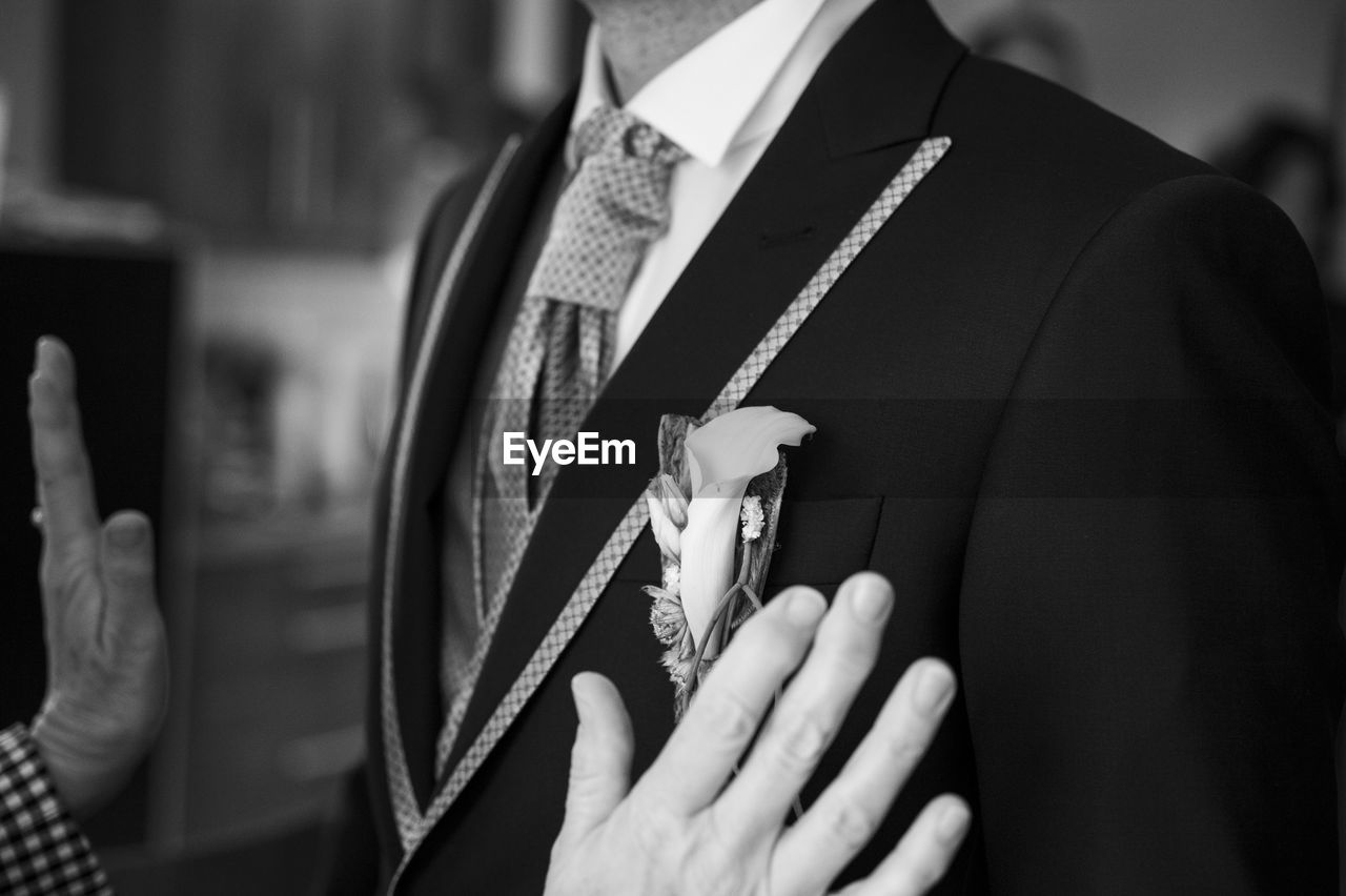 real people, human hand, hand, midsection, focus on foreground, holding, human body part, clothing, men, religion, lifestyles, belief, day, adult, indoors, suit, finger