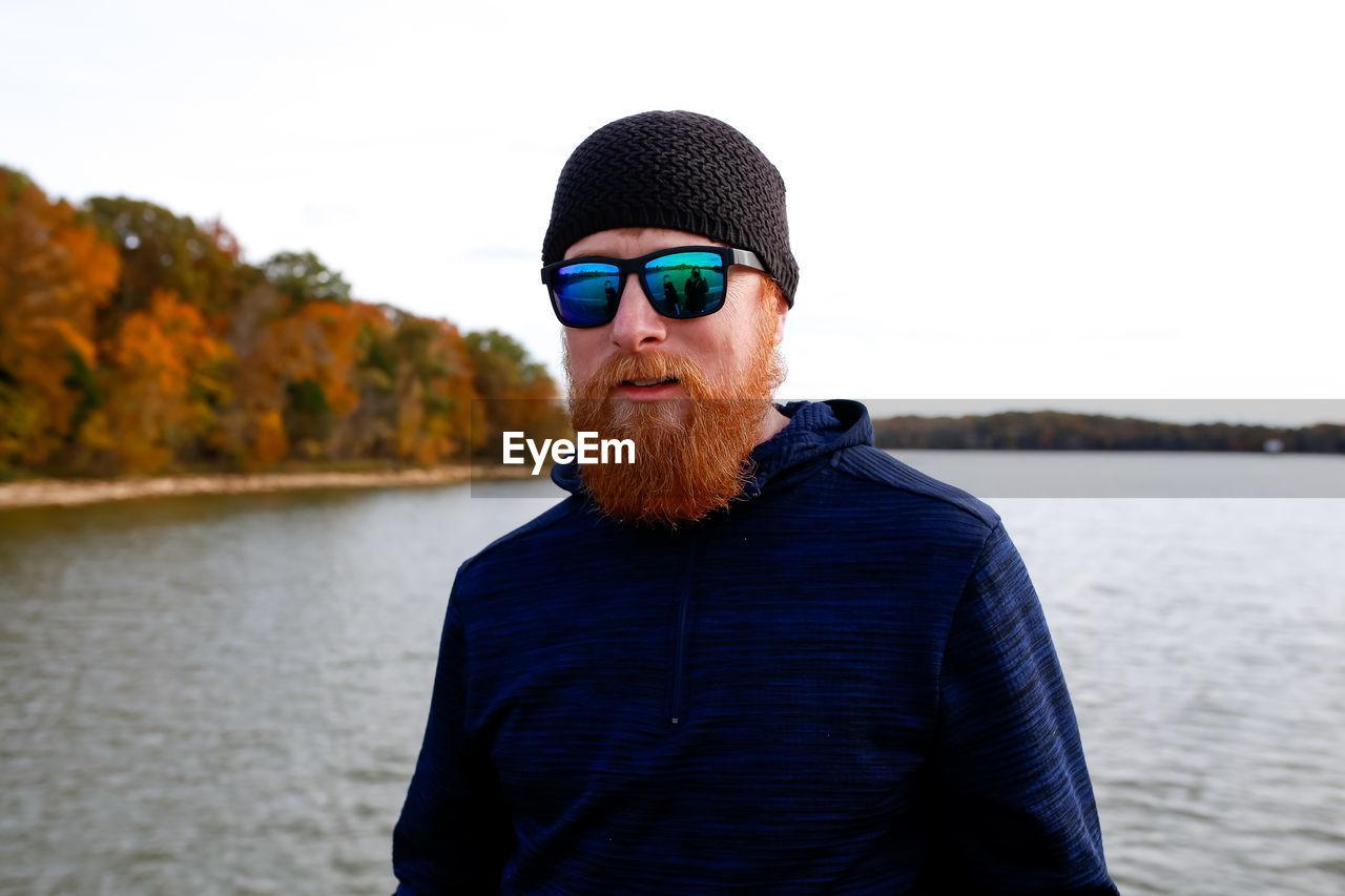Portrait of bearded man standing against lake