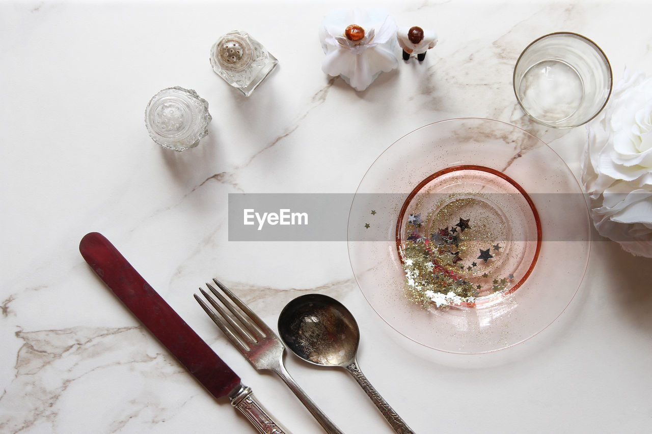 High Angle View Of Eating Utensils With Stars And Glitters By Statues On Floor
