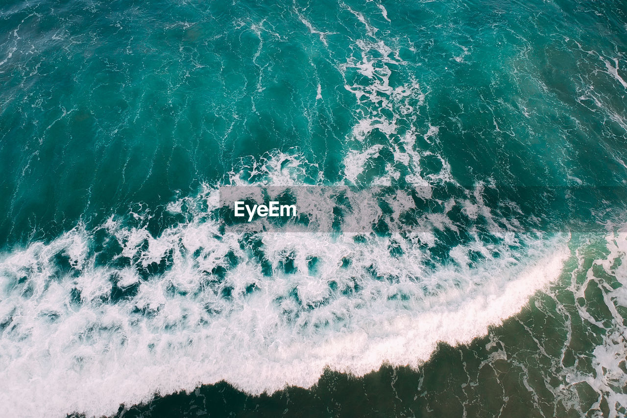 sea, water, wave, sport, motion, surfing, aquatic sport, nature, beauty in nature, day, high angle view, outdoors, waterfront, land, close-up, rushing, beach, scenics - nature, power in nature, turquoise colored, flowing water