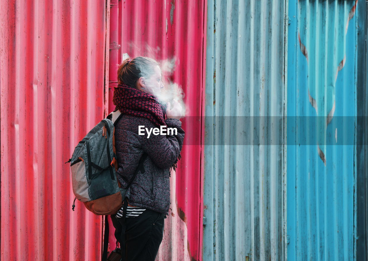 Side View Of Young Woman Smoking Against Metal Sheets