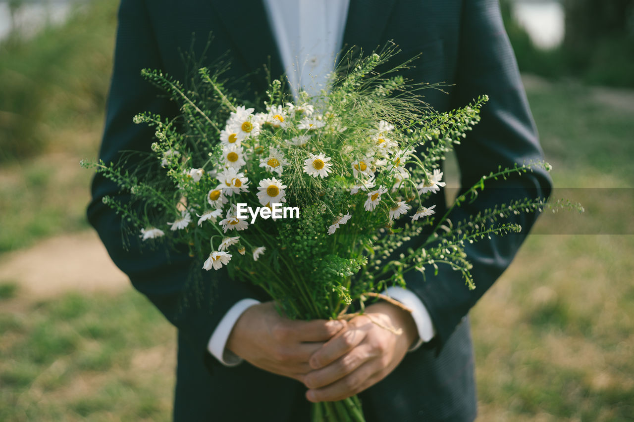 plant, flower, flowering plant, real people, holding, one person, hand, nature, focus on foreground, human hand, vulnerability, freshness, day, beauty in nature, fragility, midsection, growth, lifestyles, men, outdoors, flower head, flower arrangement, bouquet, bunch of flowers
