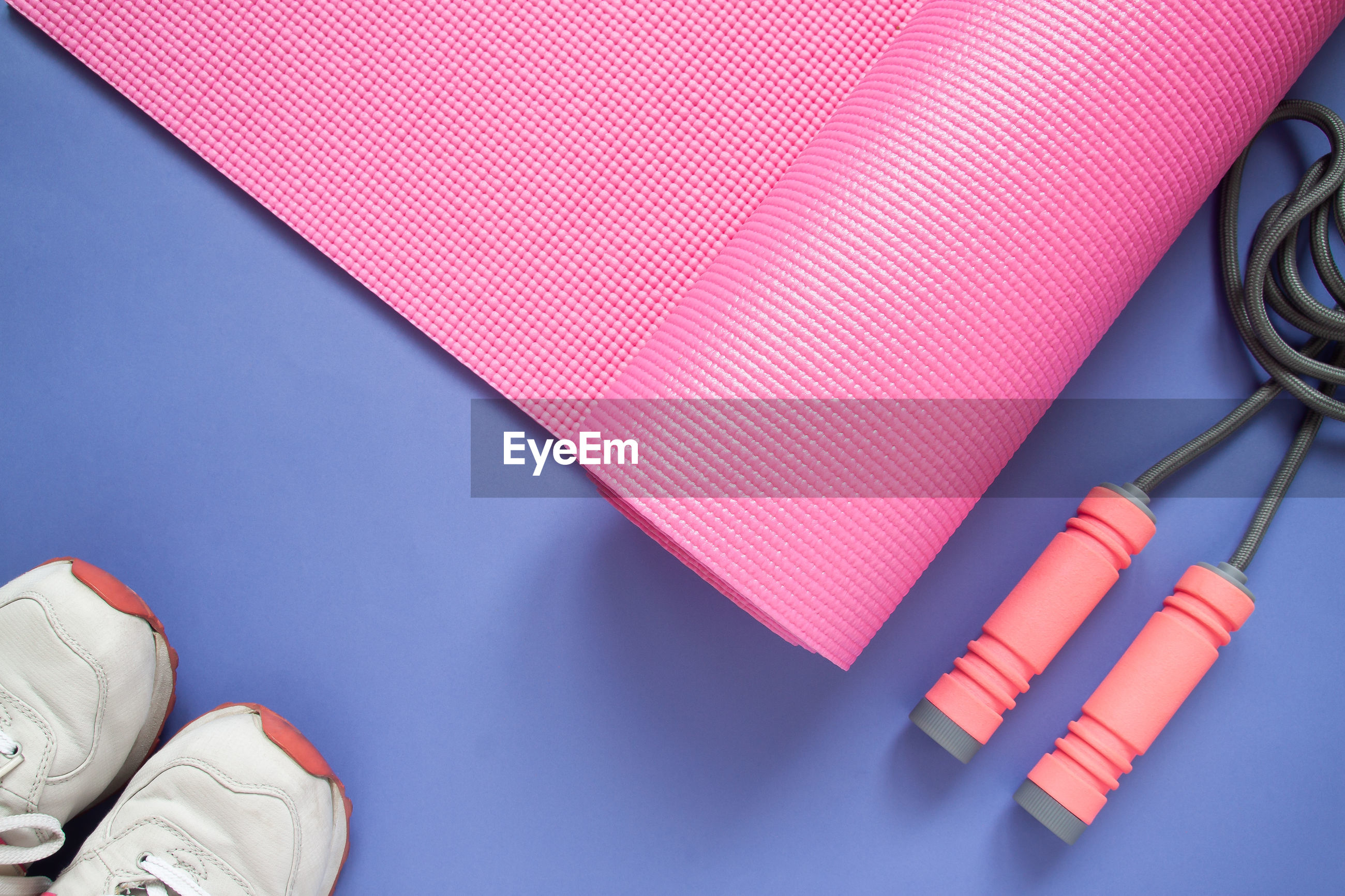 High angle view of exercise mat and shoes on purple background