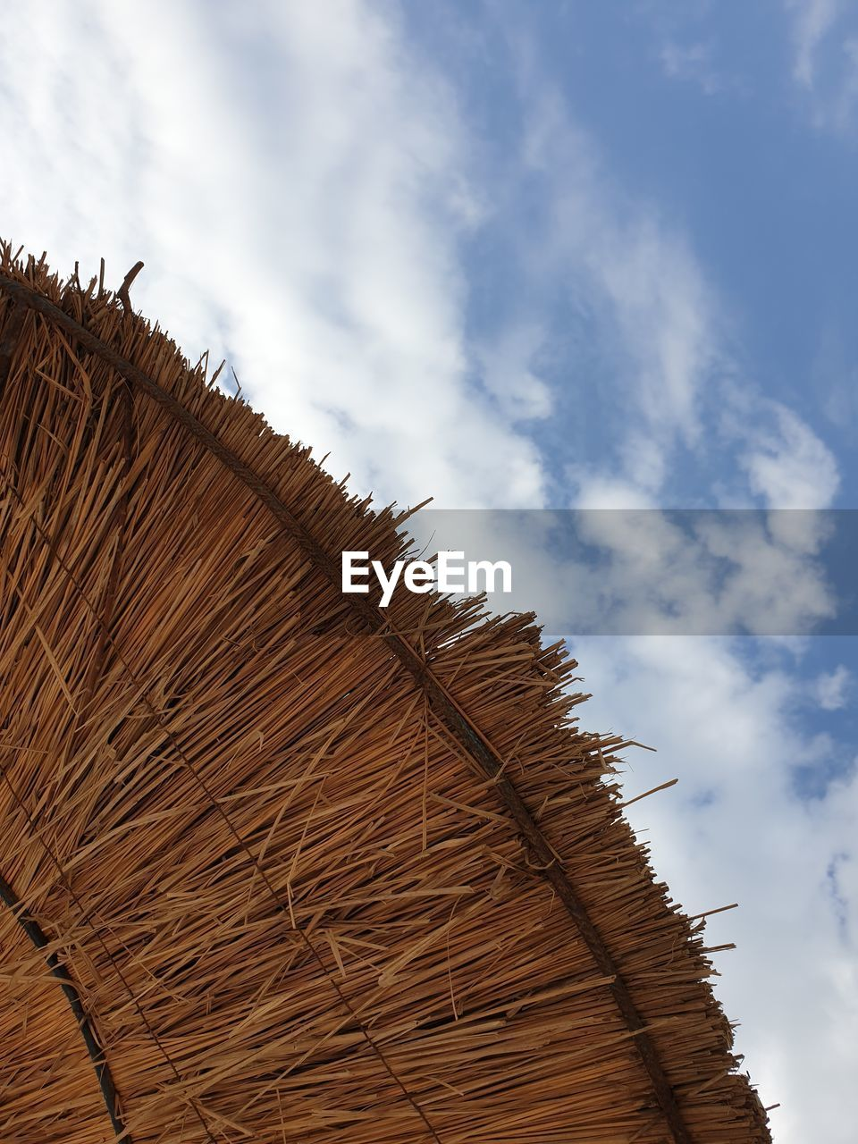 LOW ANGLE VIEW OF HAY BALES ON ROOF AGAINST SKY