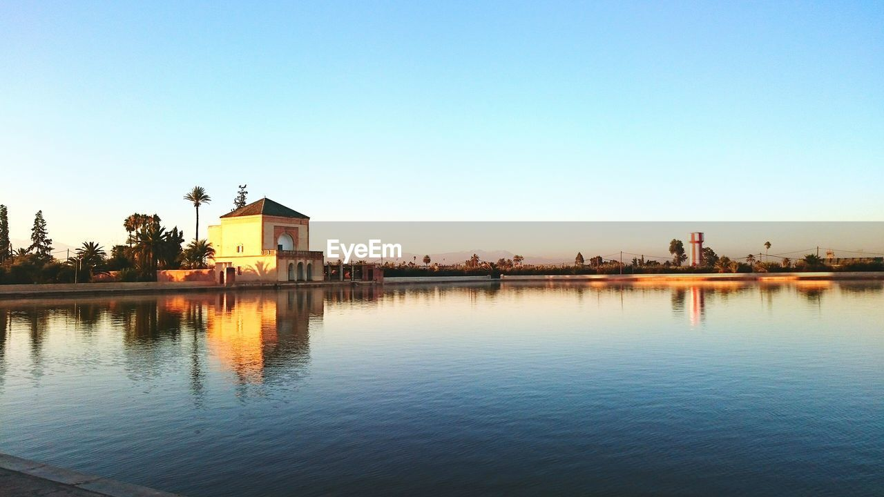 sky, architecture, built structure, water, building exterior, waterfront, clear sky, copy space, reflection, nature, building, no people, beauty in nature, lake, scenics - nature, day, tranquility, outdoors, blue