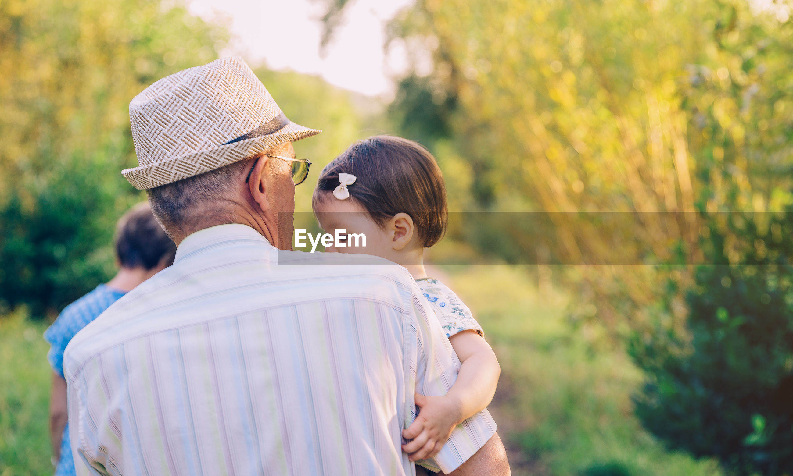 Rear view of grandfather carrying granddaughter while standing at park
