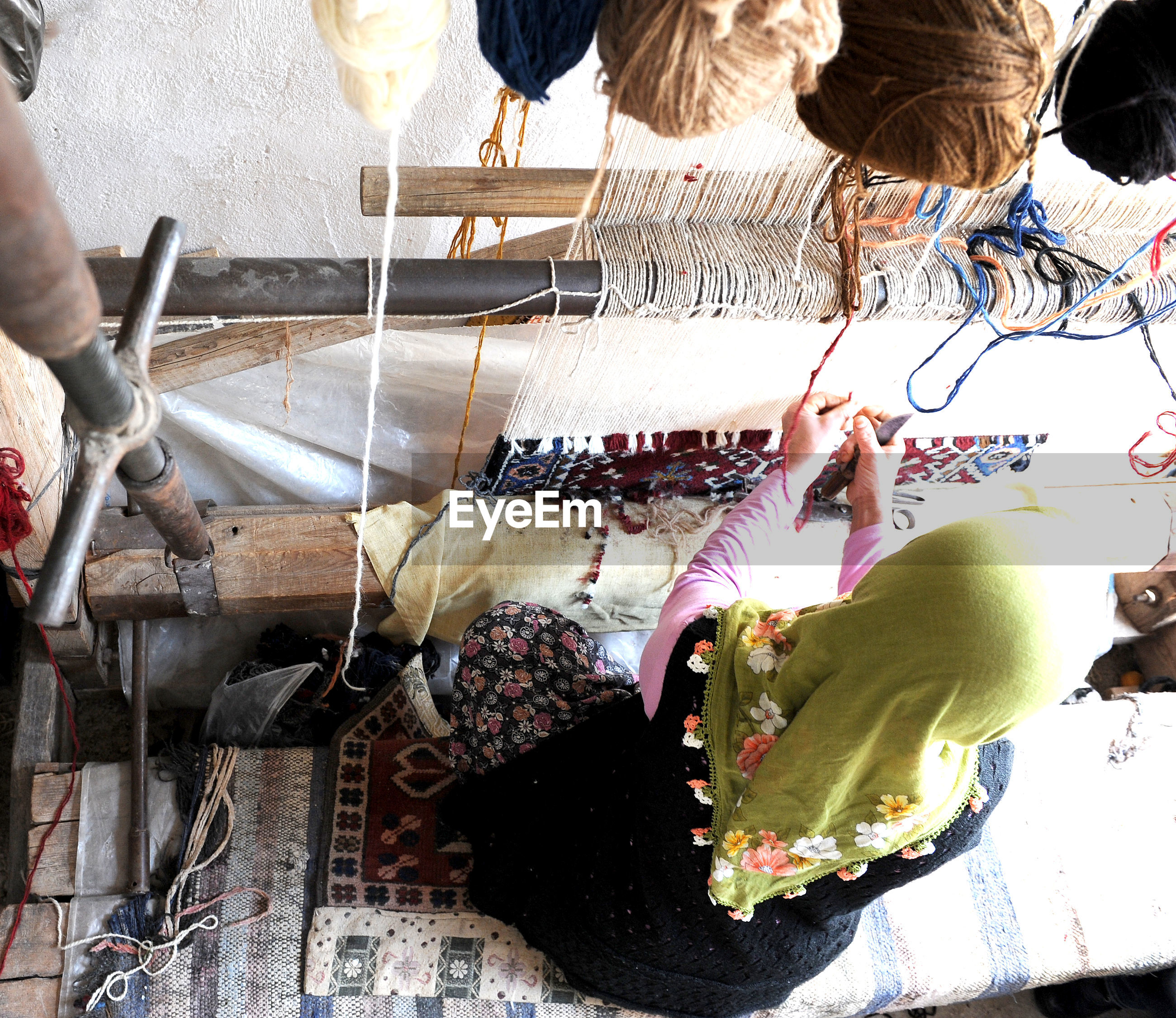 High angle view of woman weaving carpet