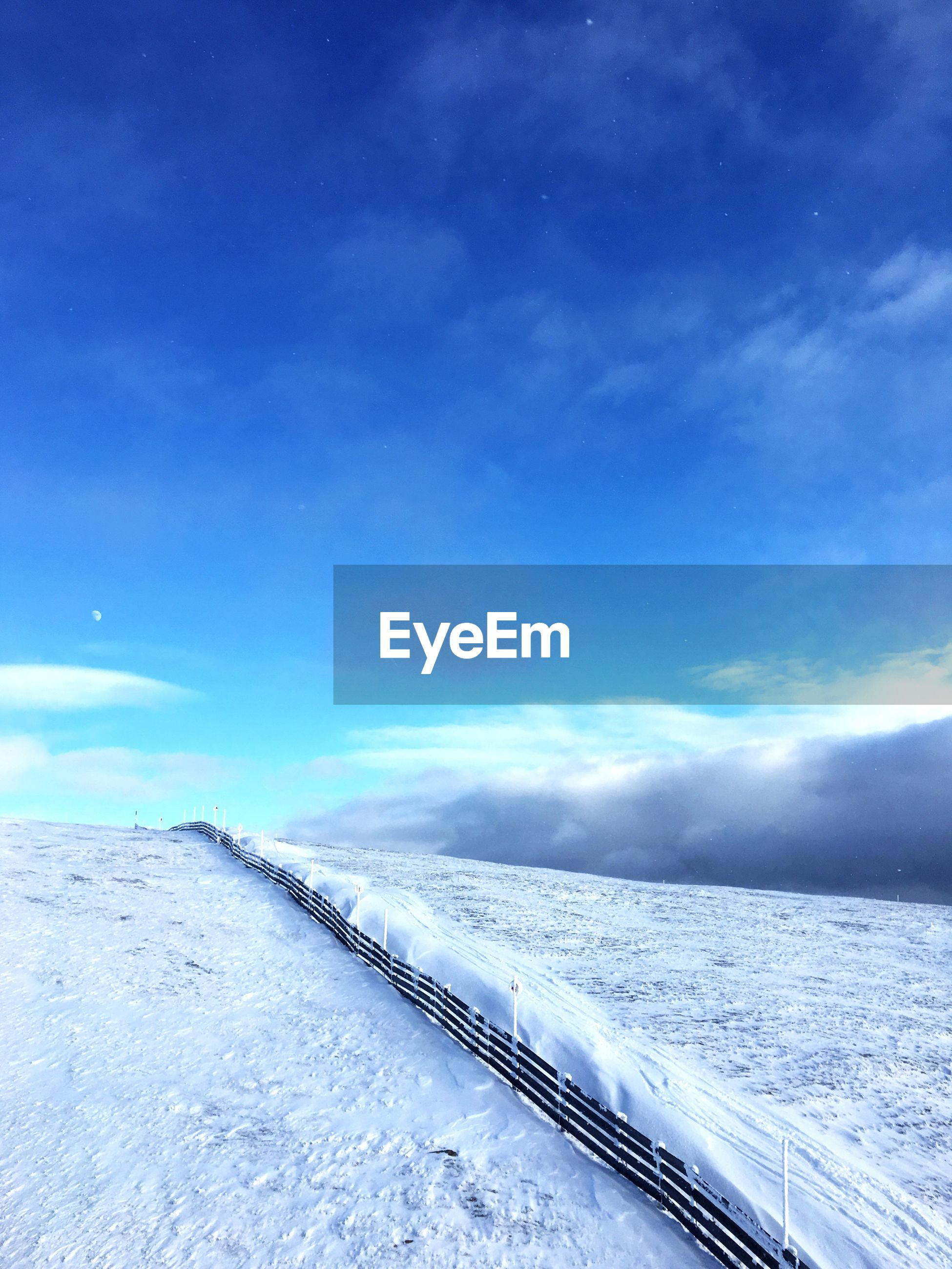 Scenic view of landscape against blue sky during winter