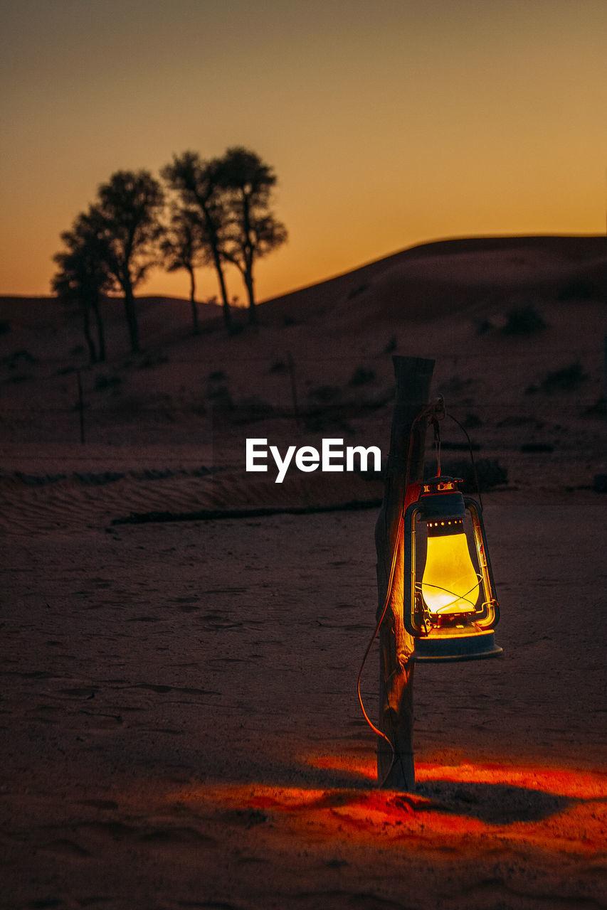 Lantern hanging on wooden post during sunset