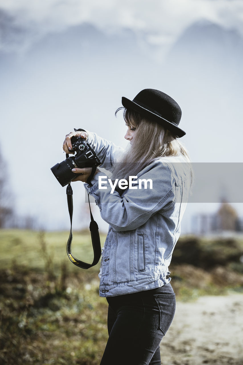 Side View Of Young Woman Photographing Through Camera Against Sky