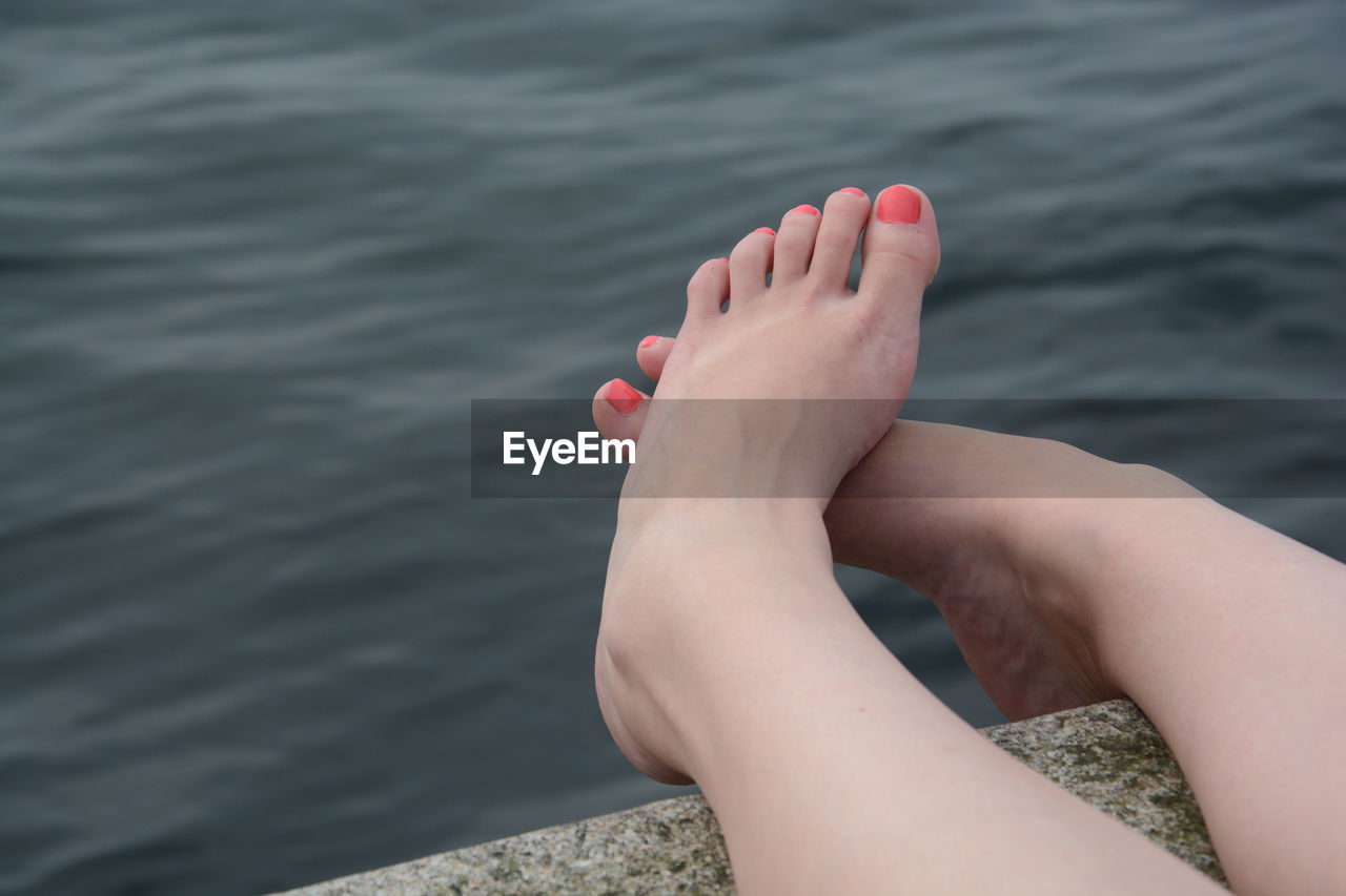 Low Section Of Woman Relaxing On Pier By Lake
