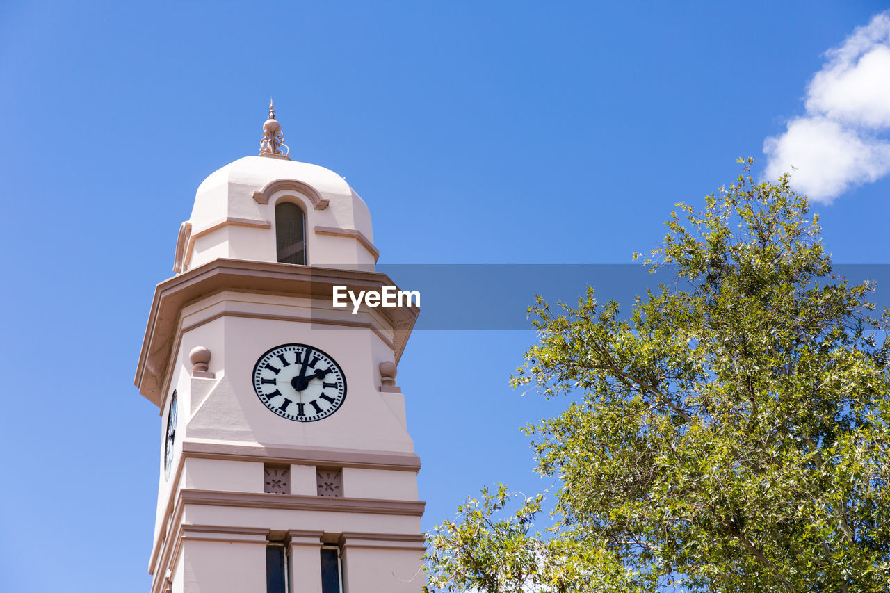 clock, sky, time, architecture, low angle view, building, tower, building exterior, built structure, clock tower, plant, tree, nature, blue, no people, day, religion, clear sky, place of worship, belief, clock face, outdoors, minute hand