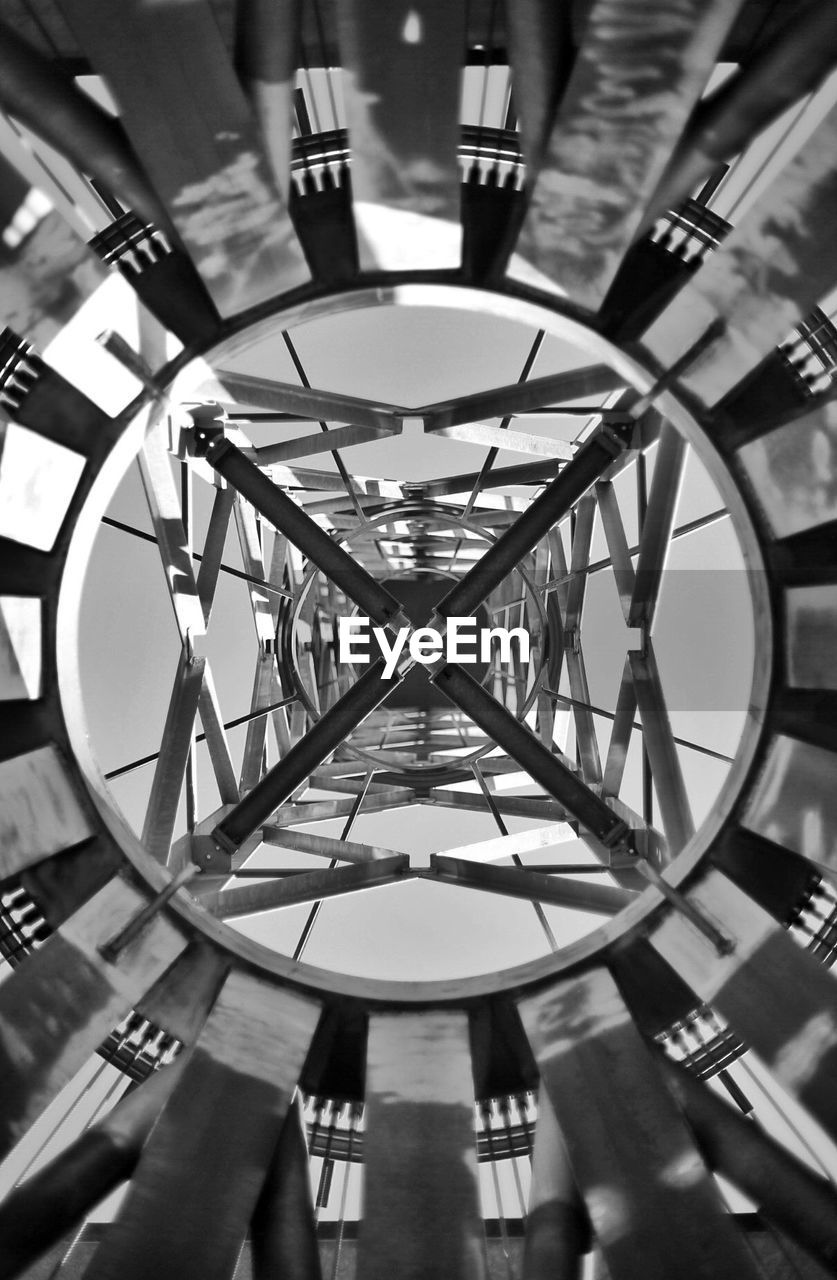 indoors, built structure, architecture, ceiling, geometric shape, shape, pattern, circle, hanging, no people, focus on foreground, lighting equipment, illuminated, low angle view, design, close-up, day, reflection, metal, directly below, clock