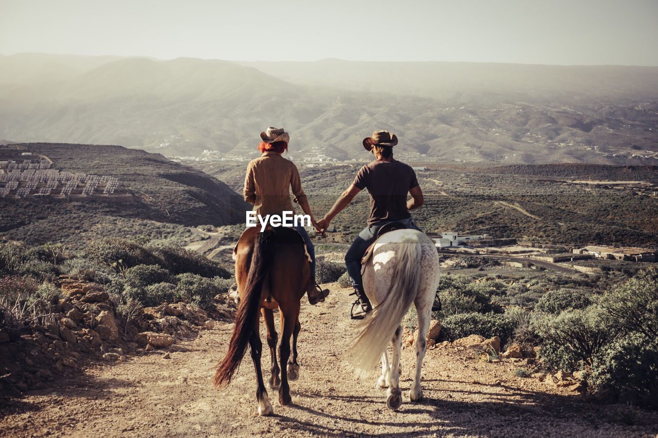 Couple Riding Horses On Dirt Road