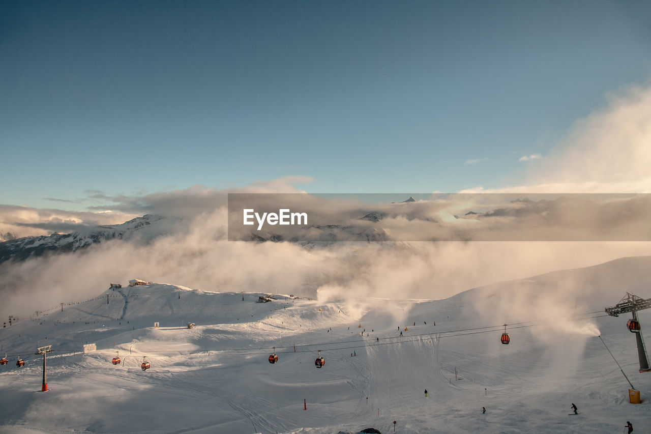 Scenic View Of Ski Lift Over Snowcapped Mountain Against Sky