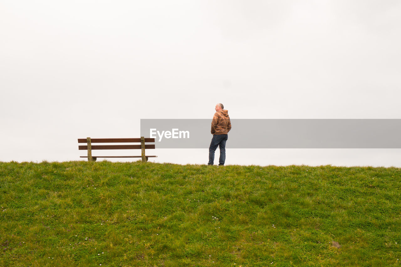 full length, plant, one person, grass, nature, rear view, field, real people, land, lifestyles, leisure activity, standing, casual clothing, sky, green color, beauty in nature, men, adult, copy space, outdoors