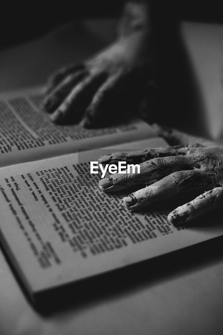 CLOSE-UP OF HUMAN HAND ON BOOK IN TABLE