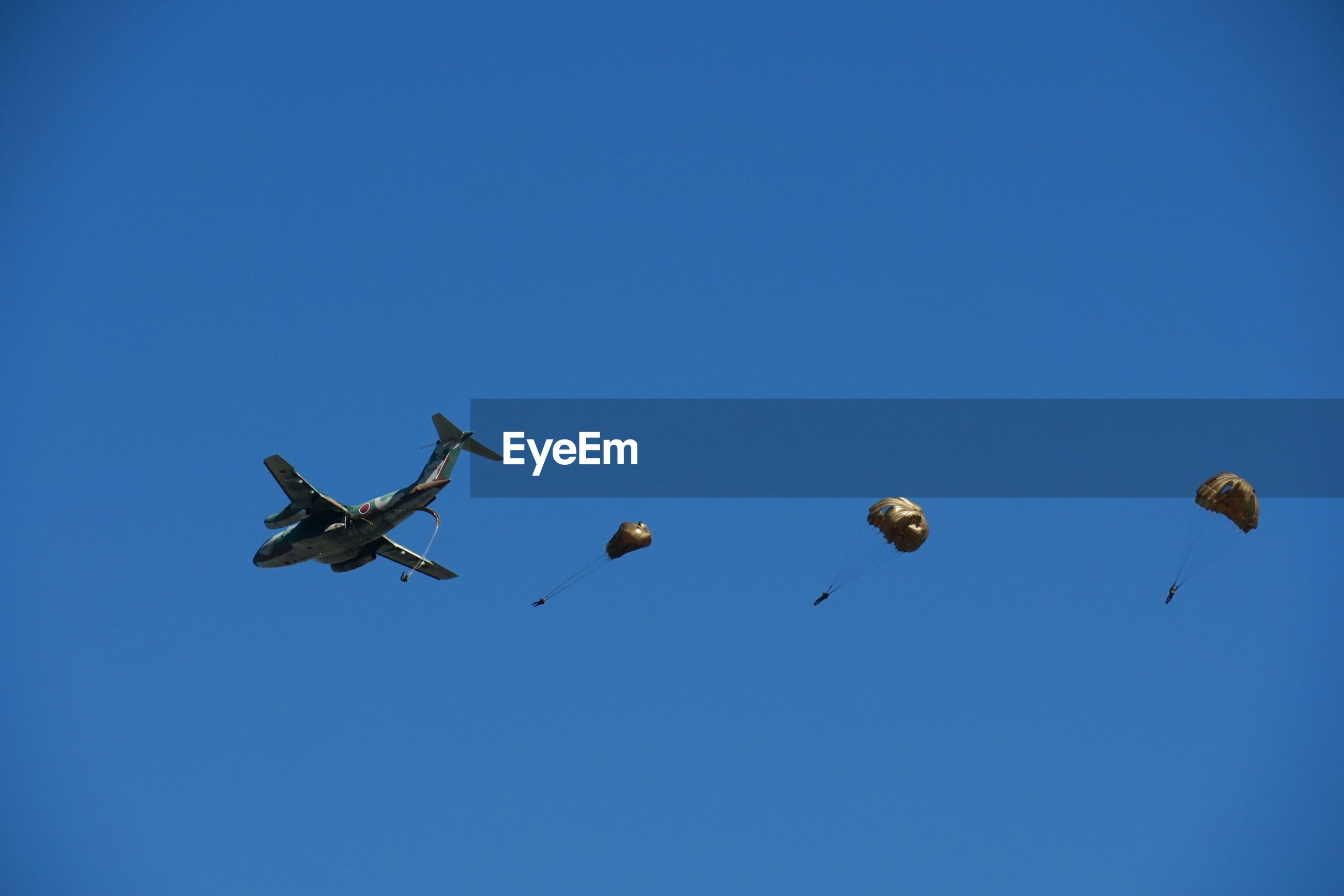 Low angle view of airplane and parachutes against clear blue sky