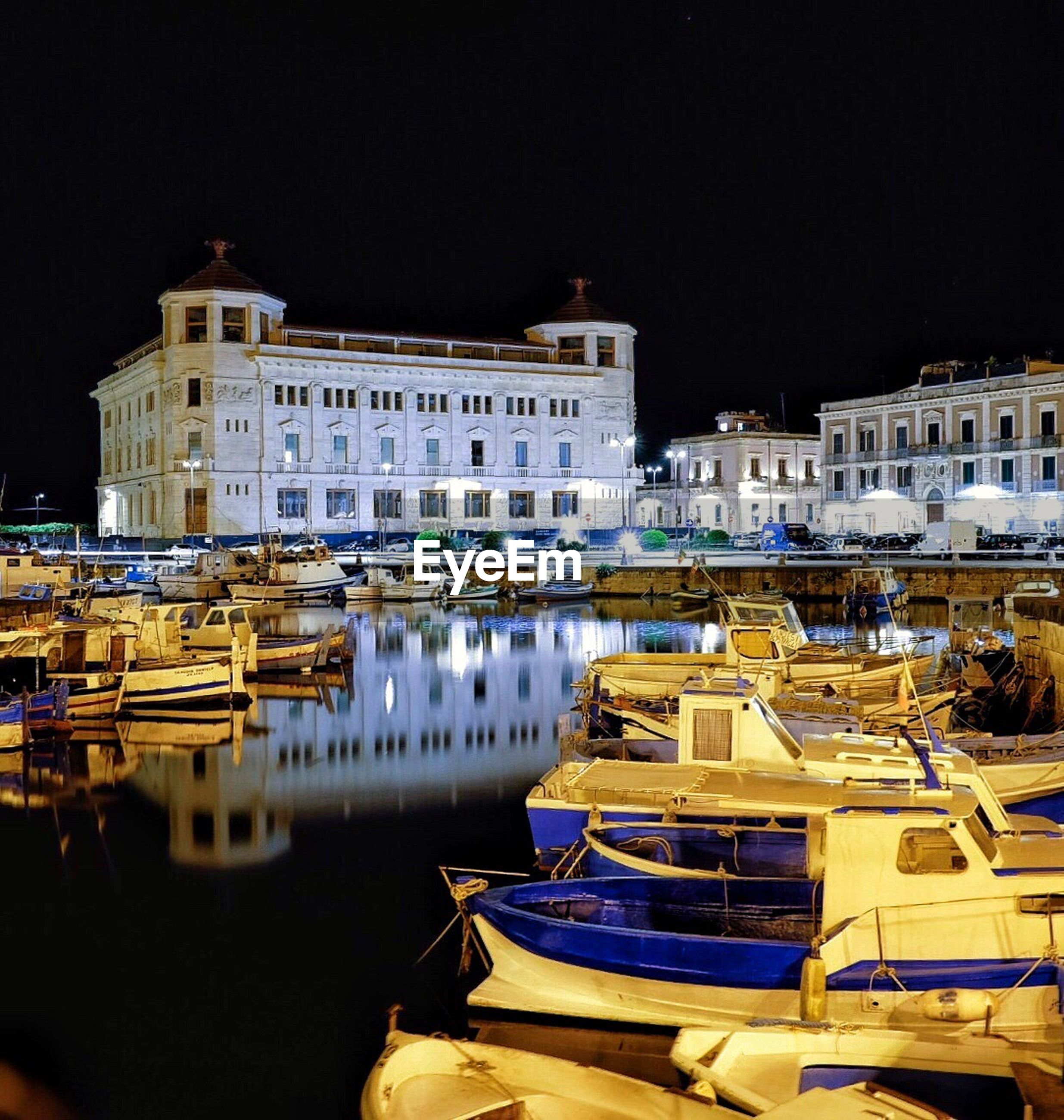 BOATS MOORED IN FRONT OF LAKE AT NIGHT