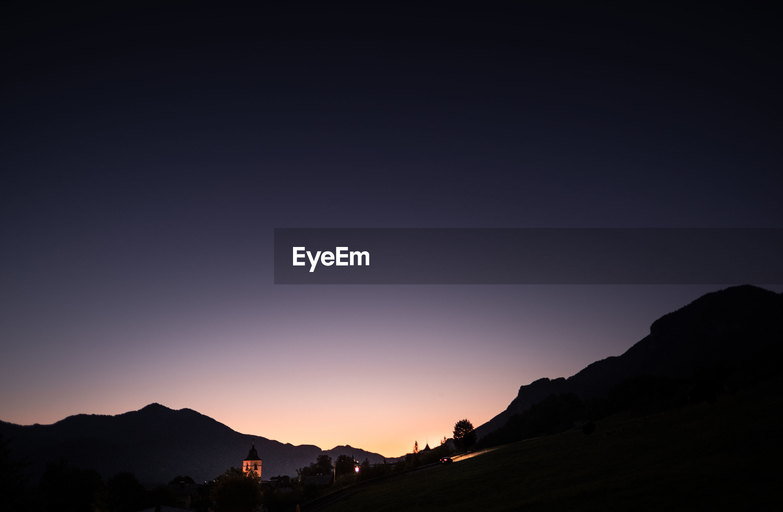 Scenic view of silhouette mountains against clear sky during sunset