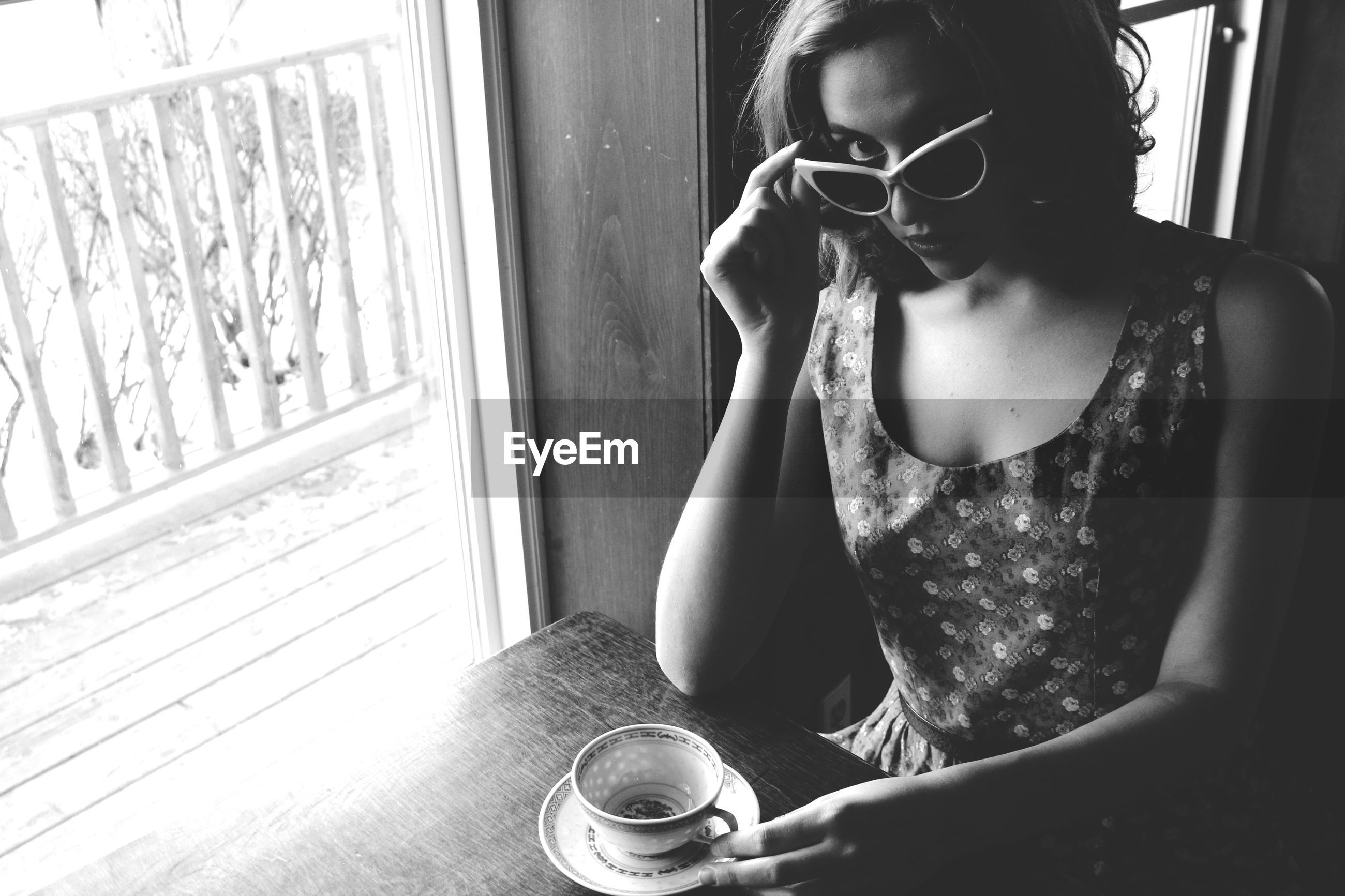 indoors, window, home interior, young adult, sitting, young women, lifestyles, person, front view, glass - material, sunglasses, domestic room, window sill, house, day, domestic life, looking at camera, casual clothing