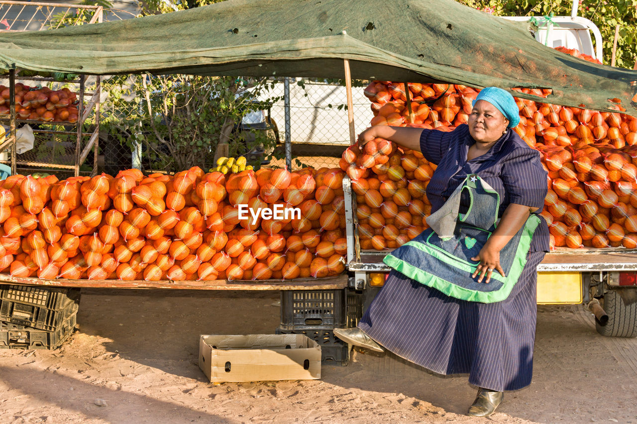 Full Length Of Vendor Sitting Against Food At Market Stall
