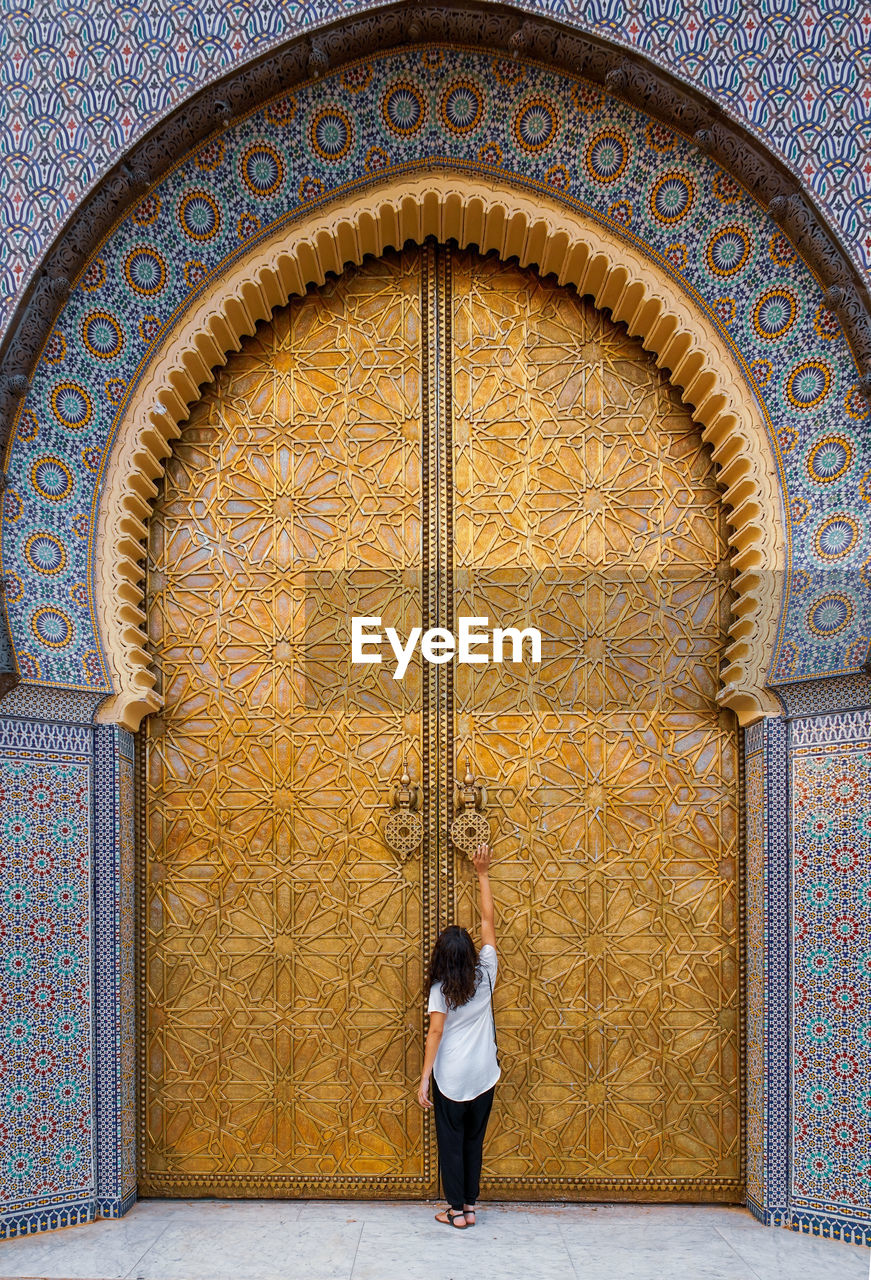 architecture, built structure, real people, one person, building exterior, entrance, door, day, arch, full length, women, building, leisure activity, rear view, casual clothing, adult, lifestyles, wall - building feature, standing, pattern, outdoors, ornate