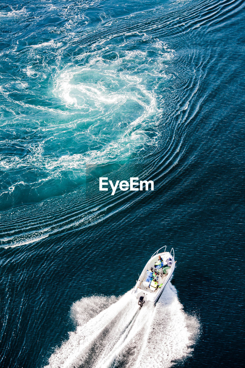 High Angle View Of People Traveling In Yacht On Sea