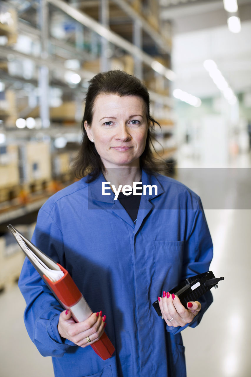 PORTRAIT OF A SMILING YOUNG WOMAN STANDING IN FACTORY