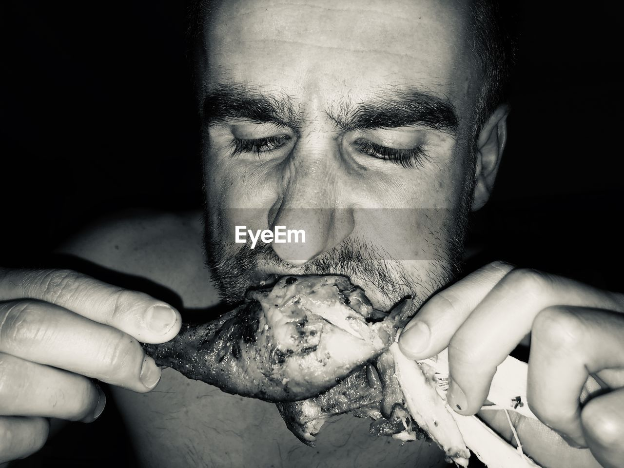 Close-up of man eating chicken