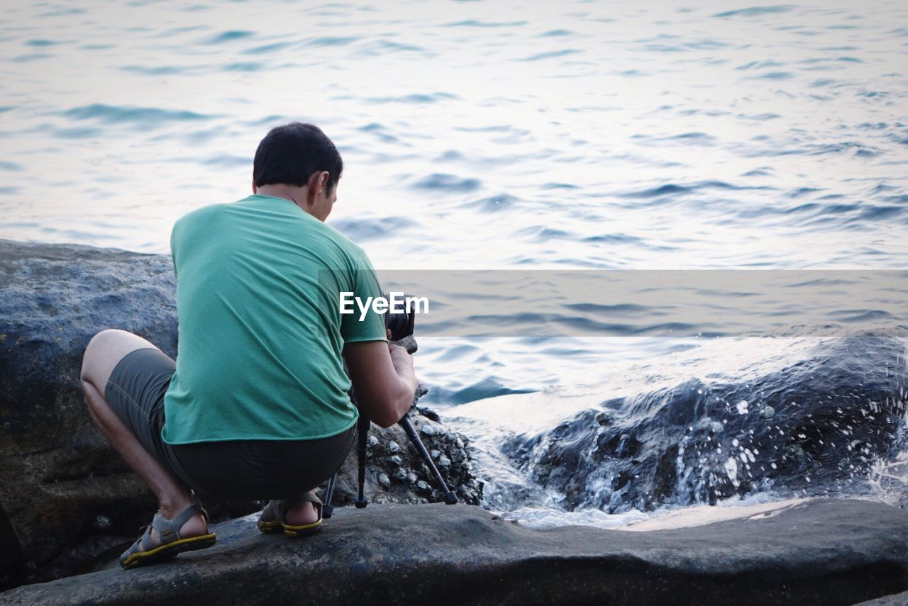 Rear View Of Man Crouching While Photographing On Rocky Shore