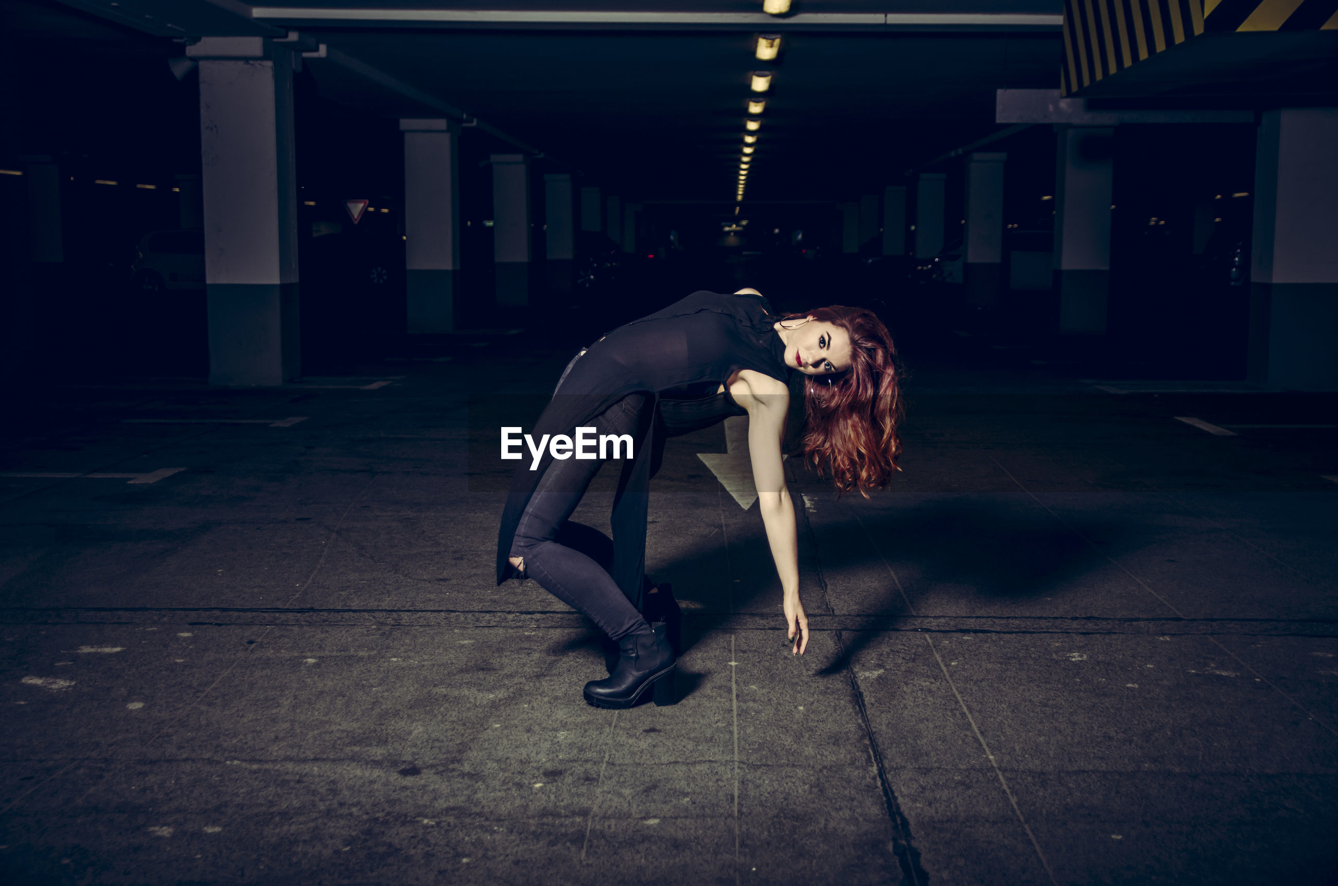 Redhead woman bending over backwards in parking lot at night