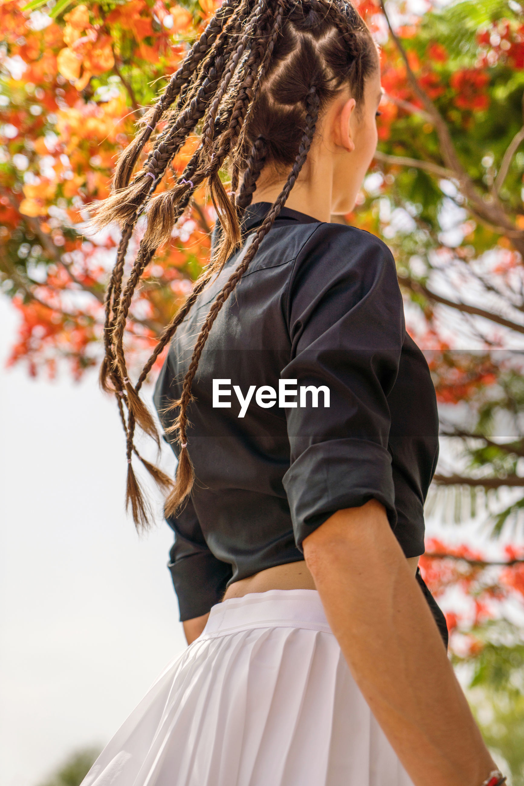 Midsection of woman standing by tree having her hair braided and wearing a stylish outfit