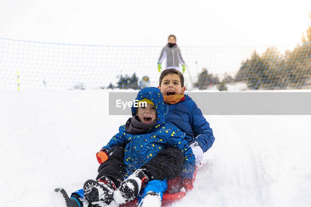 Full length of siblings tobogganing on snow during winter