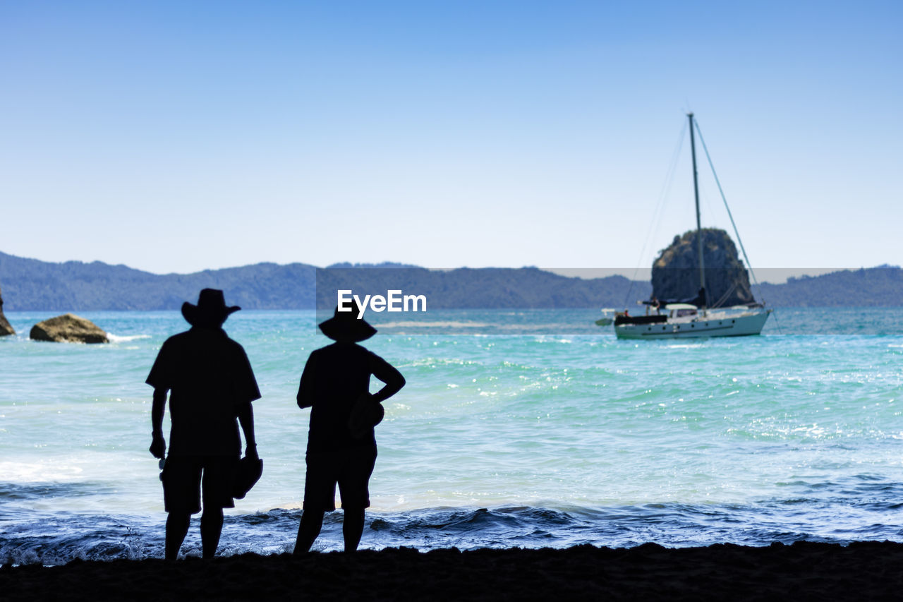 sea, water, sky, real people, two people, men, leisure activity, nature, lifestyles, scenics - nature, land, nautical vessel, beauty in nature, clear sky, beach, rear view, standing, mountain, people, sailboat, outdoors, couple - relationship