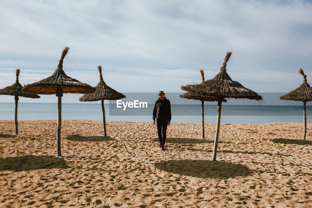 Full Length Of Man Walking On Sand Against Sea At Beach
