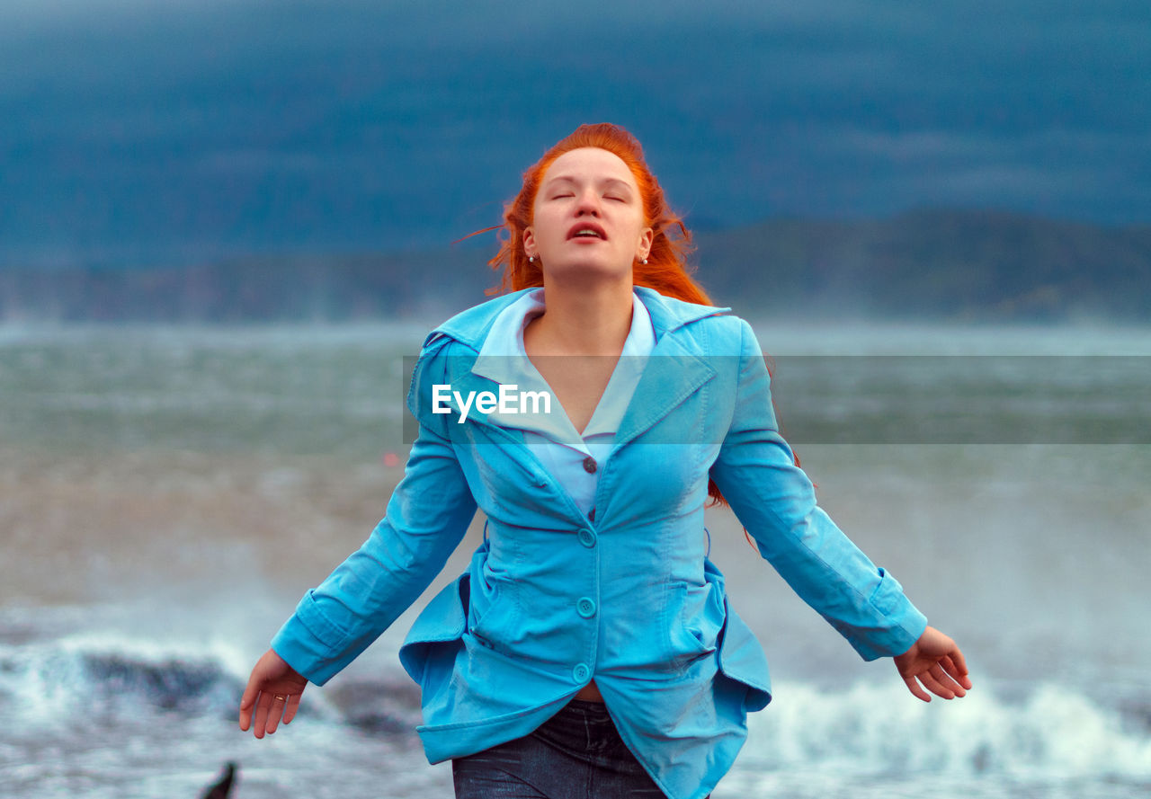 Carefree Young Woman With Eyes Closed Standing At Beach