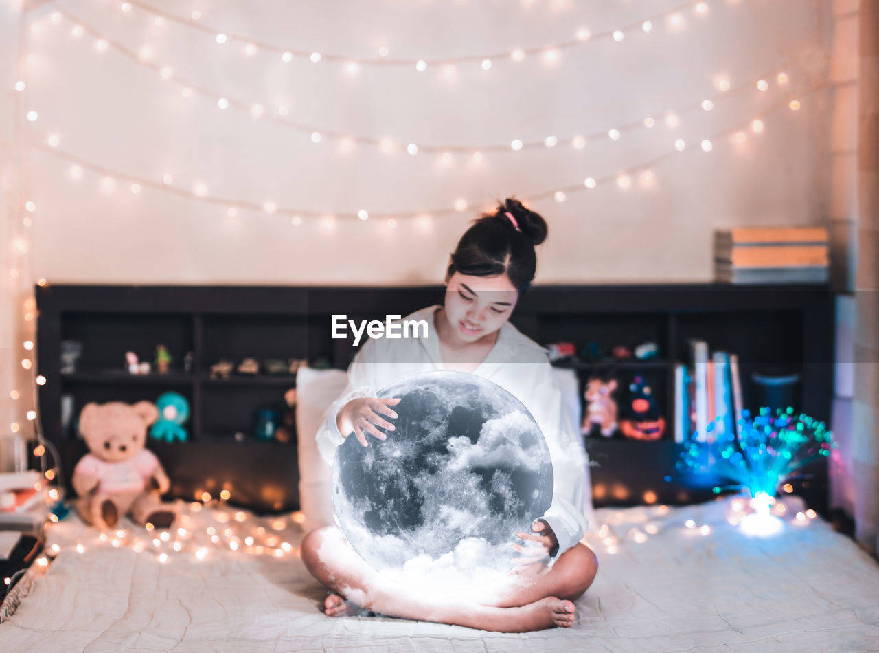 Digital Composite Image Of Young Woman Sitting With Moon On Bed