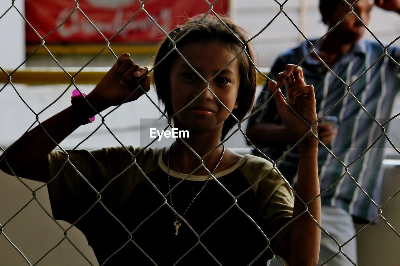 PORTRAIT OF WOMAN HOLDING CHAINLINK FENCE